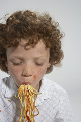 Young boy eating spaghetti indoors