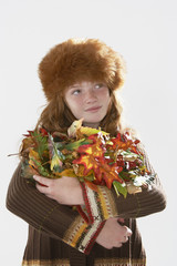 Young girl indoors holding armful of leaves