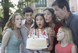 Six people outdoors blowing out candles on a birthday cake