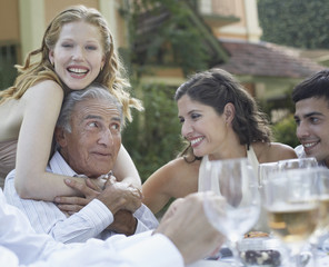 Four people at outdoor party smiling and being affectionate