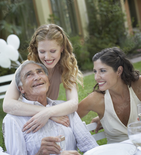 Three people at outdoor party smiling and being affectionate