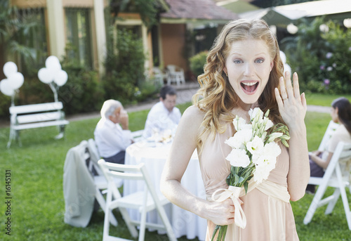 Woman standing at outdoor party with flowers showing off new ring smiling