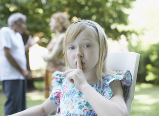 Young girl sitting outdoors with finger to lips shushing