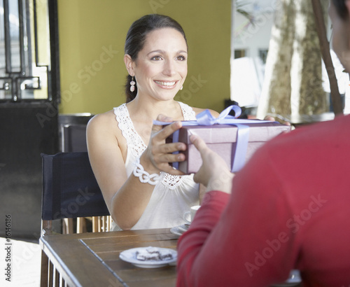 Woman in restaurant giving man a gift and smiling
