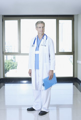 Doctor in hospital corridor standing by large window with clipboard