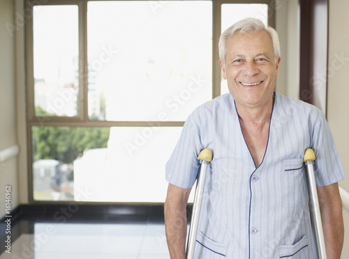 Senior man in hospital corridor using crutches and smiling