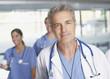 Doctor standing in hospital corridor smiling
