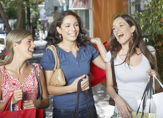 Three women outdoors carrying shopping bags and smiling