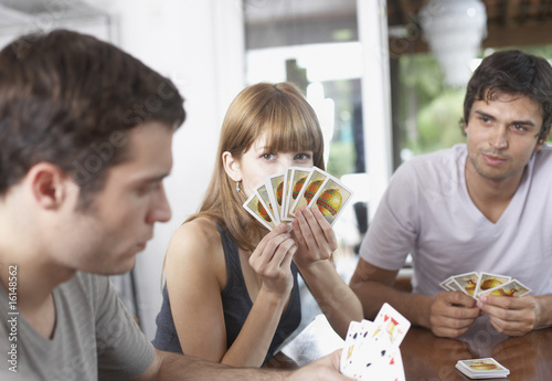 Three people playing cards at table