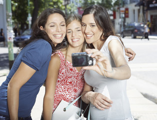 Three women outdoors taking self-portrait with digital camera smiling
