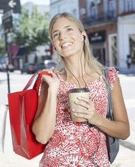 Woman outdoors with shopping bags listening to music and smiling