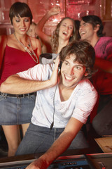 Disc jockey in nightclub with people dancing around him smiling