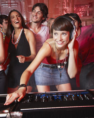 Disc jockey in nightclub with people dancing around her smiling