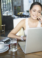 Woman in restaurant using laptop and smiling