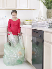 Young girl in kitchen putting recyclable materials into a bag smiling