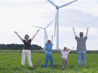 Family standing outdoors by windmills with arms up in air
