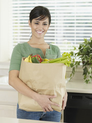 Woman in kitchen holding grocery bag and smiling