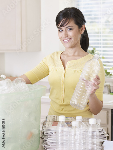 Woman in kitchen with recyclable materials and bin smiling