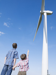 Two young boys outdoors pointing at a windmill