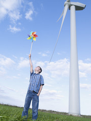 Young boy outdoors holding a toy windmill by a real windmill
