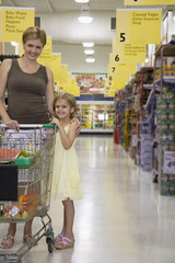 Woman and young girl in grocery store with shopping cart smiling