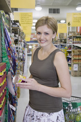 Woman in grocery store aisle holding can smiling