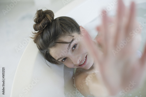 Woman relaxing in bubble bath hiding behind hand and smiling