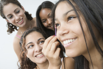 Teen girls doing makeup