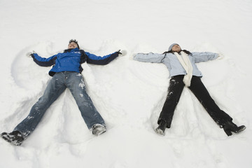 Young couple making angels in the snow