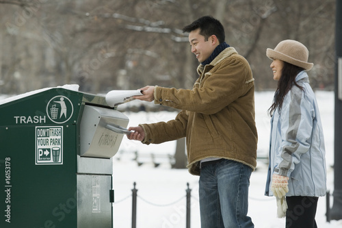 Couple using a trash dispenser