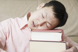 Asian teen boy sleeping on books
