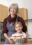 Woman and young girl in kitchen holding plate of cherry cupcakes and smiling