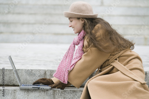 Young woman using her laptop outside