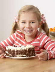 Young girl in kitchen eating cake and making a mess smiling
