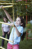 Young girl outdoors at playground climbing with senior woman in background