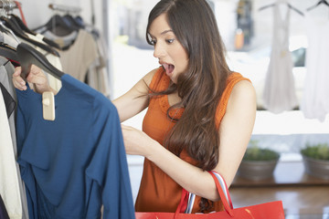 Woman in store looking at a shirt in shock