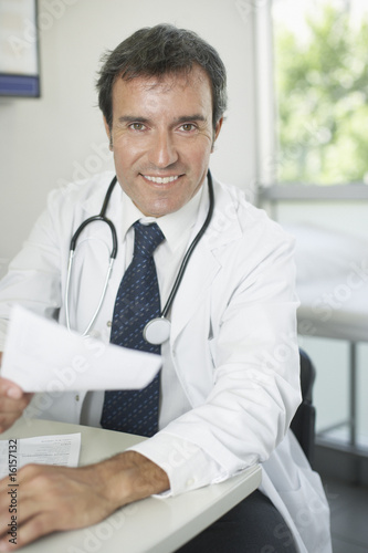 Doctor sitting in office with paperwork smiling