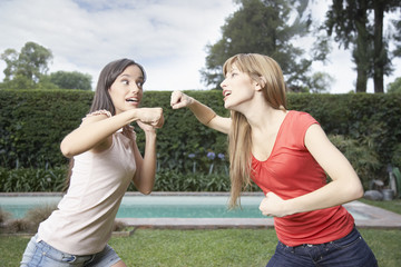 Two women outdoors playfighting