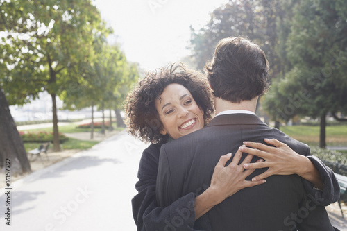 Couple embracing outdoors in park smiling