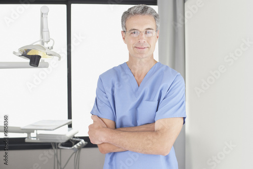 Dentist standing in examination room smiling