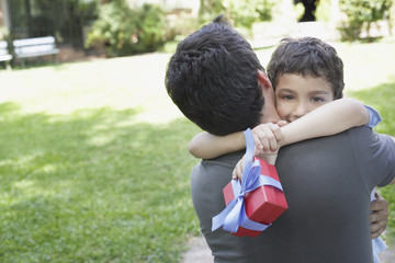 Man outdoors embracing young boy holding gift