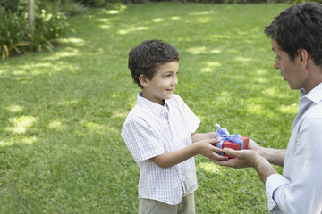 Man outdoors giving smiling young boy gift