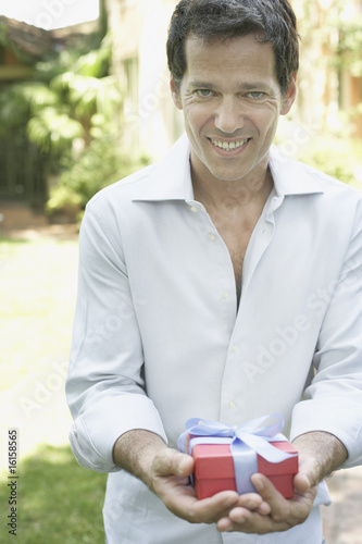 Man standing outdoors holding gift and smiling