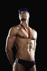 Swimmer with gold medal wearing cap and goggles