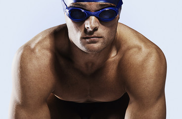 Swimmer wearing cap and goggles on his mark
