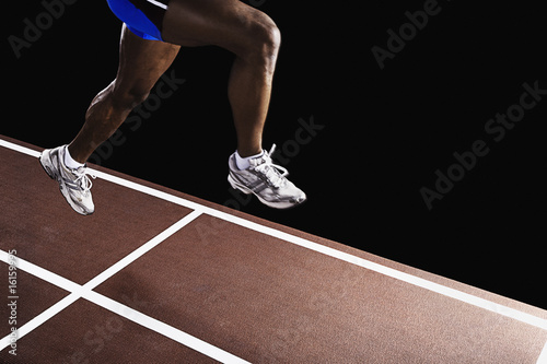 Runner on race track jumping up in air