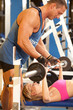 Trainer assisting woman at gym