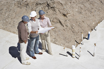 Construction workers viewing blueprints on construction site