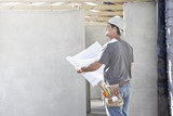 Construction worker reviewing blueprints at construction site