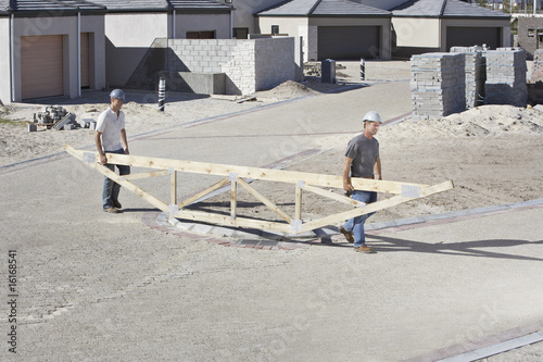 Construction workers carrying roof truss at construction site